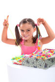 Girl making a bead necklace — Stock Photo