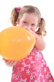 Young girl in a pink flowery dress with a yellow balloon — ストック写真