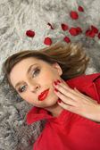 Woman lying surrounded by rose petals — Stock Photo