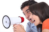 Young couple shouting into a megaphone — Stock Photo