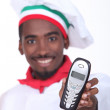 A black chef handing a phone. — Stock Photo