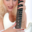 Blond woman holding electric guitar — Stock Photo #9770688