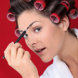 图库照片: Womwith curlers putting on makeup