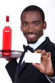 Wine waiter holding forth a business card left blank for your details — Stock Photo