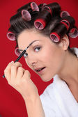 Woman with curlers putting on makeup — Stock Photo
