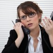 Stressed office worker with two telephones - Stock Photo