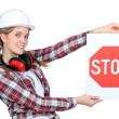 Female construction worker holding stop sign - Stock Photo