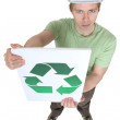 Young man holding sign with symbol of recycling — Stock Photo