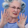 Stock Photo: Elder upset with curlers in her hair