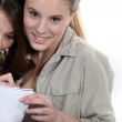 Two teenage girls writing on note pad — Stock Photo #9782938