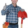Manual worker with gloves and spade giving thumbs-up — Stock Photo
