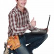 Happy builder with laptop giving the thumbs-up — Stock Photo #9784369