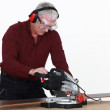 Craftsman cutting a board with an electric saw — Stock Photo #9785069