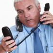 Overwhelmed white collar worker answering telephones - Stock Photo