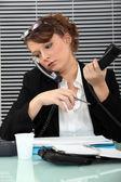 Secretary burdened with two phones — Stock Photo