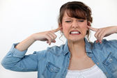Woman covering her ears — Stock Photo