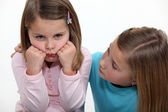 A little girl trying to cheer up her sister. — Stock Photo