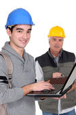 A trainee manual worker with a laptop. — Stock Photo