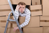 Man stuck behind stacks of cardboard boxes — Stock Photo