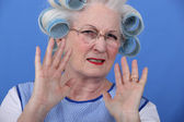 Elder upset with curlers in her hair — Stock Photo