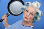 Elderly lady attacking with frying pan — Stock Photo