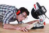 Man positioning a plank of wood in a mitre saw — Stok fotoğraf