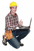 Happy builder with laptop giving the thumbs-up — Stock Photo