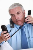 Overwhelmed white collar worker answering telephones — Stock Photo