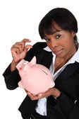 Black businesswoman with piggybank — Stockfoto