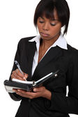 Fed-up businesswoman writing in her agenda — Stockfoto
