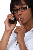 Woman making shush gesture whilst using telephone — Stock Photo