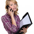 Stock Photo: Womwith folder making telephone call