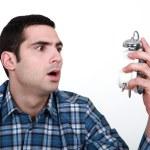 Shocked man with an alarm clock — Stock Photo