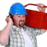 Tradesman pretending to listen to music — Stock Photo