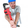 Chubby plumber holding adjustable wrench — Stock Photo