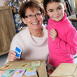 Stock Photo: Grandmother and granddaughter playing card game at Christmas