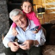 Stock Photo: Little girl playing cards with grandpa