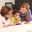 Mother and grandma reading with little girl — Stock Photo #9808761