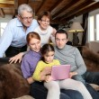 Stock Photo: Whole family around laptop