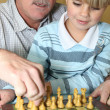 Stock Photo: Young boy playing chess with his grandfather