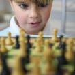 Little boy playing chess — Stock Photo