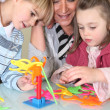 Mother and children playing a game — Stock Photo