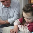 Stock Photo: Little girl with laptop and granddad watching upon her
