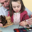 Stock Photo: Granddaughter and grandfather painting