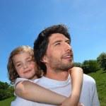Man giving daughter piggyback — Stock Photo