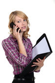 Woman with folder making telephone call — Stock Photo