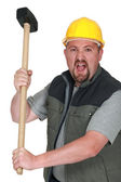 An angry tradesman holding a mallet — Stock Photo