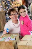 Grandmother and granddaughter playing a card game at Christmas — Foto Stock