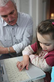 Little girl with laptop and granddad watching upon her — Stock Photo
