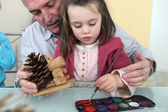 Granddaughter and grandfather painting — Stock Photo